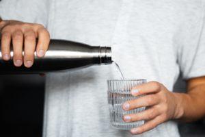 Homme buvant de l'eau conservée dans une gourde